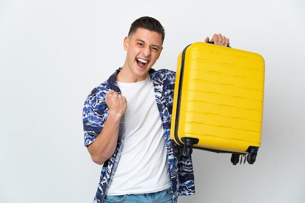 Hombre caucásico joven aislado en la pared blanca en vacaciones con maleta de viaje
