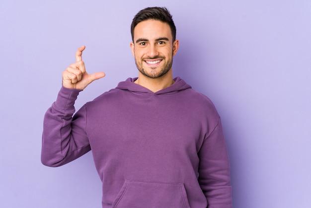 Hombre caucásico joven aislado en púrpura sosteniendo algo poco con los dedos índices, sonriente y confiado.