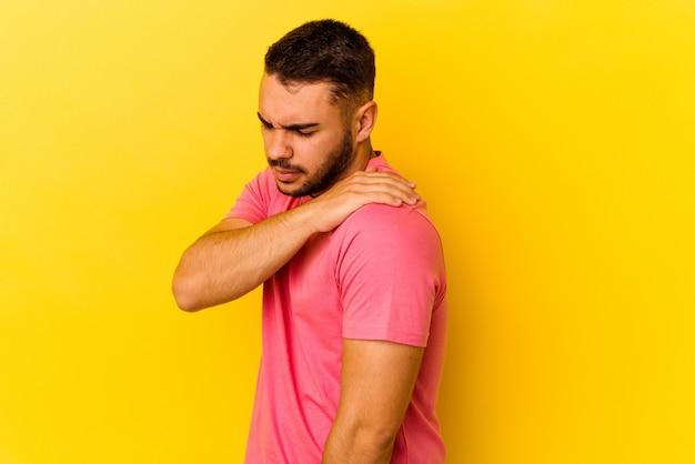 Hombre caucásico joven aislado sobre fondo amarillo con dolor de hombro.
