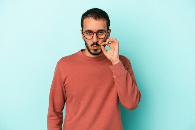 Hombre caucásico joven aislado sobre fondo azul con los dedos en los labios guardando un secreto.