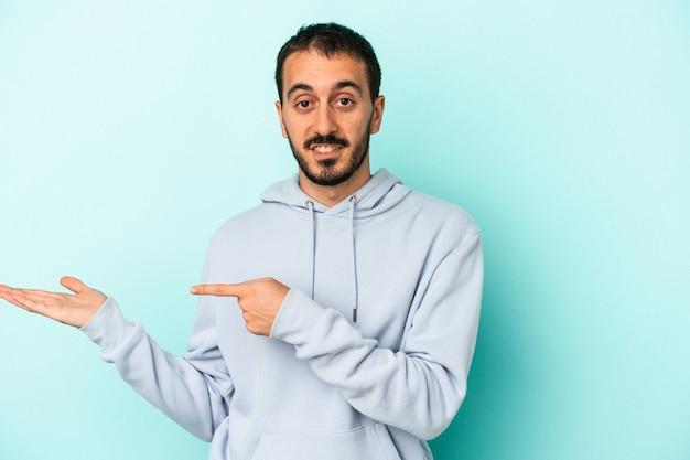 Hombre caucásico joven aislado sobre fondo azul emocionado sosteniendo un espacio de copia en la palma.