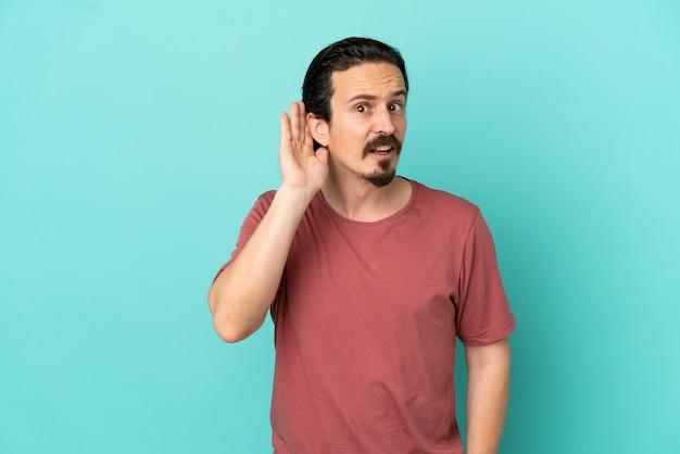 Hombre caucásico joven aislado sobre fondo azul escuchando algo poniendo la mano en la oreja