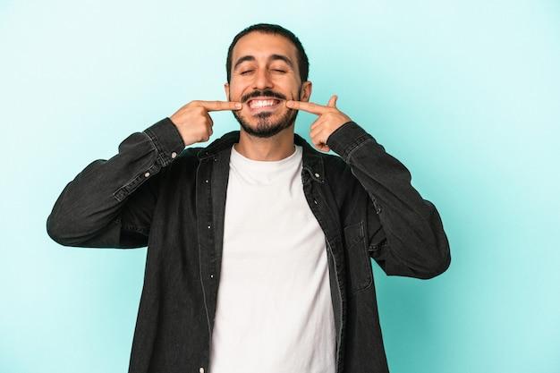 Hombre caucásico joven aislado sobre fondo azul sonríe, apuntando con el dedo a la boca.