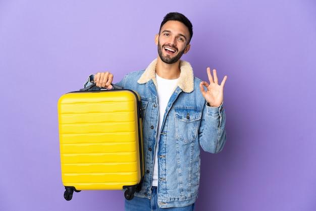 Hombre caucásico joven aislado sobre fondo azul en vacaciones con maleta de viaje y haciendo el signo de ok