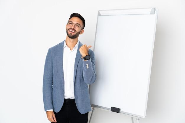 Hombre caucásico joven aislado sobre fondo blanco dando una presentación en la pizarra y con los pulgares hacia arriba