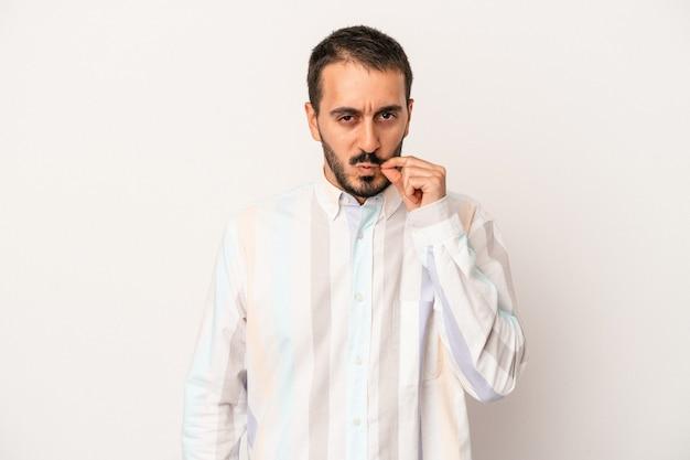 Hombre caucásico joven aislado sobre fondo blanco con los dedos en los labios guardando un secreto.