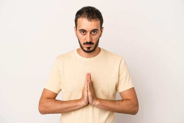 Hombre caucásico joven aislado sobre fondo blanco rezando, mostrando devoción, persona religiosa en busca de inspiración divina.