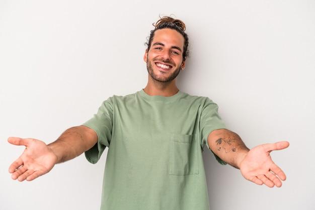Hombre caucásico joven aislado sobre fondo gris que muestra una expresión de bienvenida.