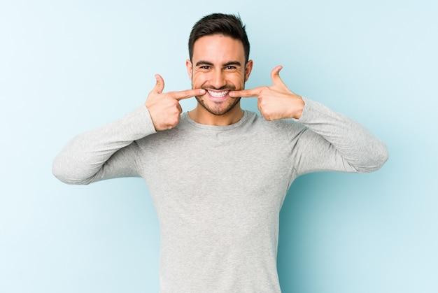 Hombre caucásico joven aislado en sonrisas azules, señalando con el dedo en la boca.