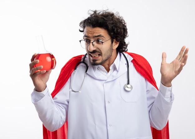 Hombre caucásico joven ansioso en gafas ópticas con uniforme médico con manto rojo y con estetoscopio alrededor del cuello se encuentra con la mano levantada mirando líquido químico rojo en frasco de vidrio