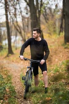 Hombre caucásico joven atractivo que monta en bicicleta en el parque. al aire libre, otoño otoño parque. copia espacio