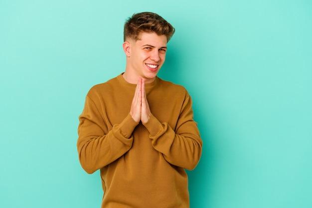 Hombre caucásico joven en azul cogidos de la mano en orar cerca de la boca, se siente confiado.