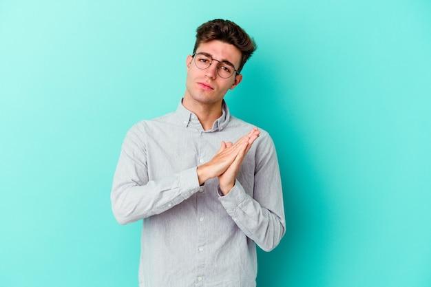 Hombre caucásico joven en azul sintiéndose enérgico y cómodo, frotándose las manos confiado.