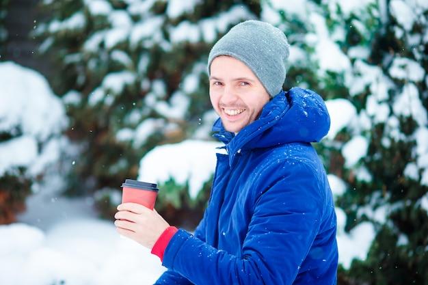 Hombre caucásico joven bebiendo café caliente en invierno congelado día al aire libre