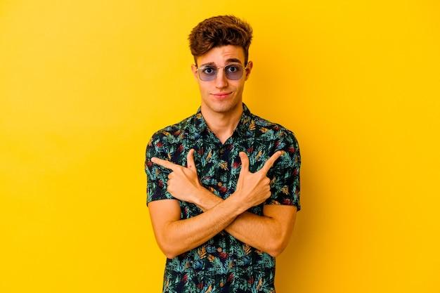 Hombre caucásico joven con una camisa hawaiana aislada en la pared amarilla apunta hacia los lados, está tratando de elegir entre dos opciones.