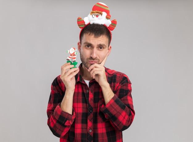 Hombre caucásico joven confundido con diadema de santa claus sosteniendo muñeco de nieve juguete de navidad mirando a cámara manteniendo la mano en la barbilla aislada sobre fondo blanco