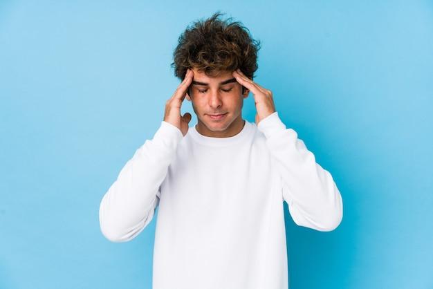 Hombre caucásico joven contra un espacio azul aislado tocar templos y tener dolor de cabeza.