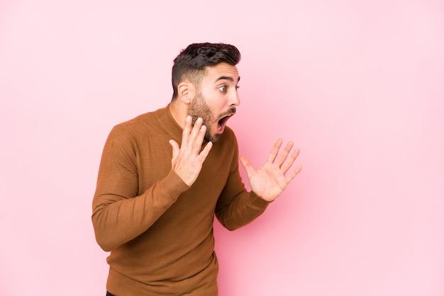 El hombre caucásico joven contra un fondo rosado aislado grita ruidosamente, mantiene los ojos abiertos y las manos tensas.