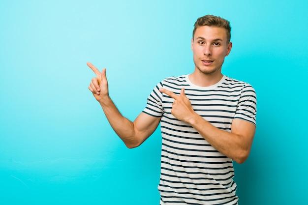 Hombre caucásico joven contra una pared azul conmocionado apuntando con los dedos índices a un espacio de copia.