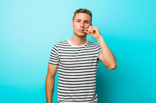 Hombre caucásico joven contra una pared azul con los dedos en los labios guardando un secreto.