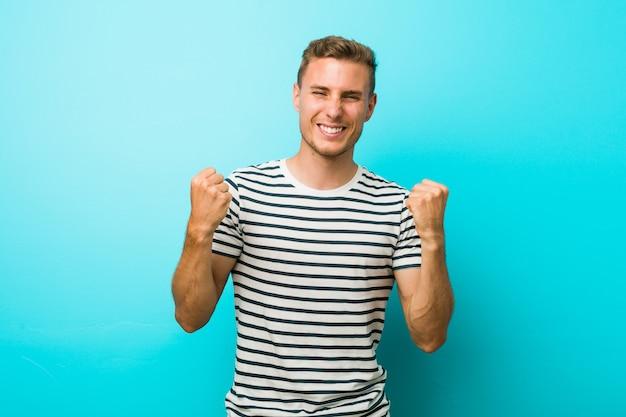 Hombre caucásico joven contra una pared azul que anima despreocupado y emocionado. concepto de victoria