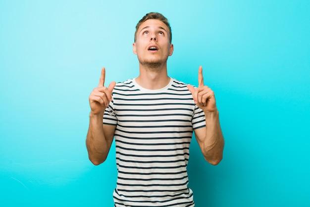 Hombre caucásico joven contra una pared azul que apunta al revés con la boca abierta.