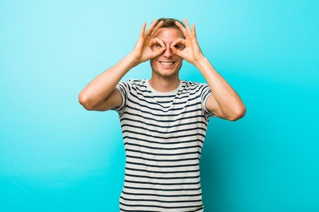 Hombre caucásico joven contra una pared azul que muestra signo bien sobre los ojos