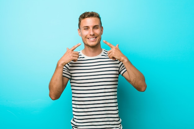 El hombre caucásico joven contra una pared azul sonríe, señalando los dedos en la boca.