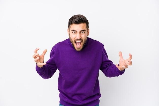 Hombre caucásico joven contra una pared blanca aislada gritando de rabia.