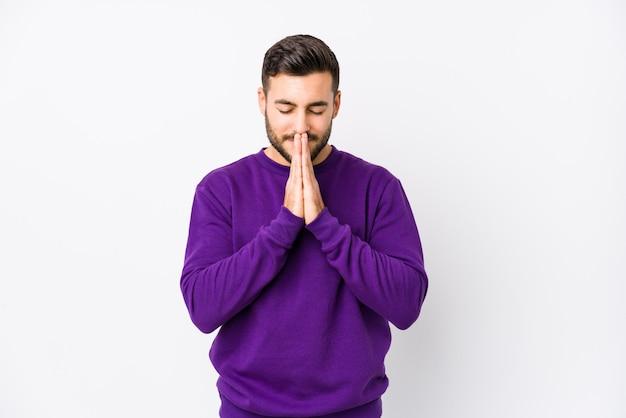 Hombre caucásico joven contra una pared blanca tomados de la mano en rezar cerca de la boca, se siente confiado.