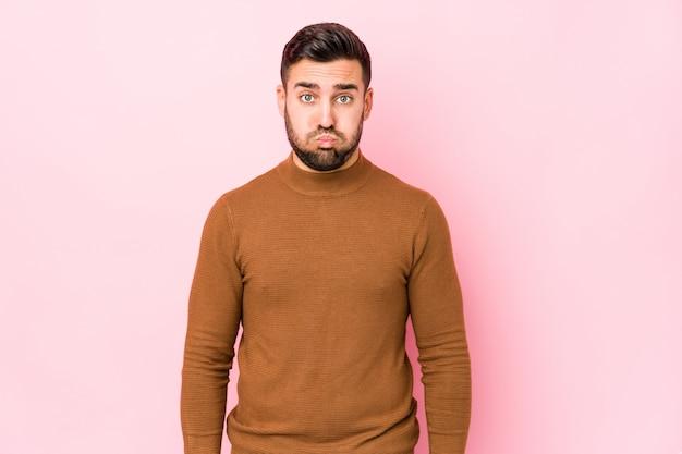 El hombre caucásico joven contra una pared rosada aislada sopla mejillas, tiene expresión cansada. concepto de expresión facial