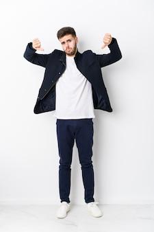 Hombre caucásico joven de cuerpo completo aislado mostrando el pulgar hacia abajo y expresando aversión.