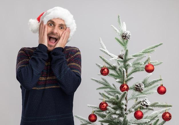 Hombre caucásico joven emocionado con sombrero de navidad de pie cerca del árbol de navidad manteniendo las manos en la cara mirando a cámara aislada sobre fondo blanco