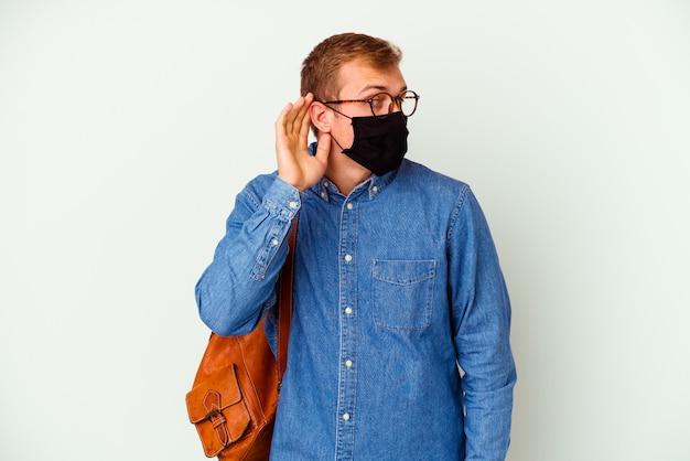 Hombre caucásico joven estudiante que estudia alemán aislado en blanco tratando de escuchar un chisme.