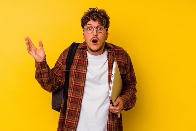 Hombre caucásico joven estudiante sosteniendo un portátil aislado sobre fondo amarillo sorprendido y conmocionado.