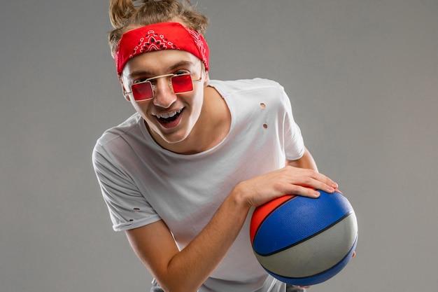 Hombre caucásico joven en gafas de sol rojas, camiseta blanca posando con balón en la pared gris
