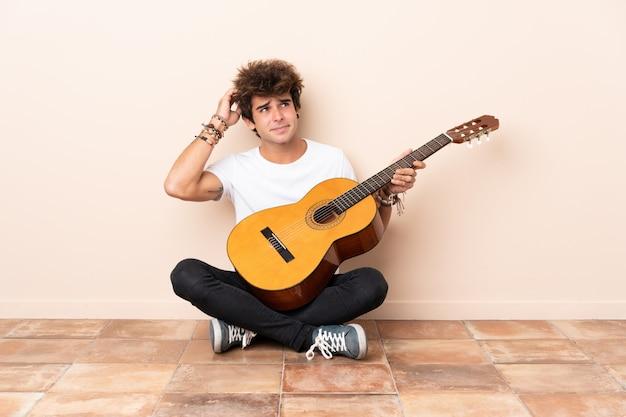 Hombre caucásico joven con una guitarra sentada en el suelo con dudas y con expresión de la cara confusa