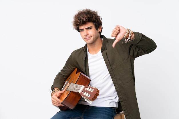 Hombre caucásico joven con guitarra sobre pared blanca aislada mostrando el pulgar hacia abajo signo