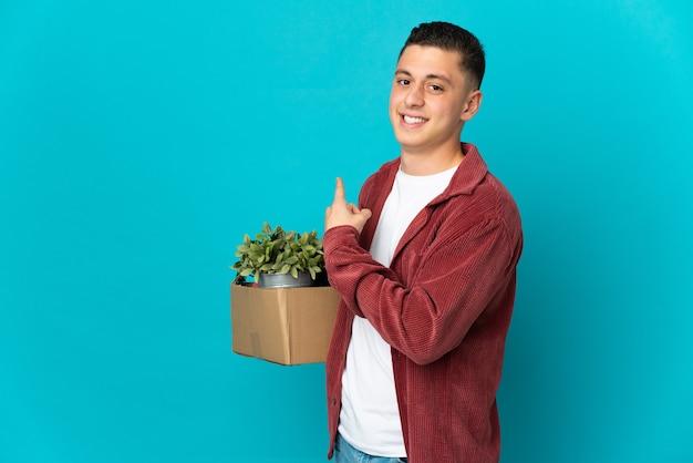 Hombre caucásico joven haciendo un movimiento mientras recoge una caja