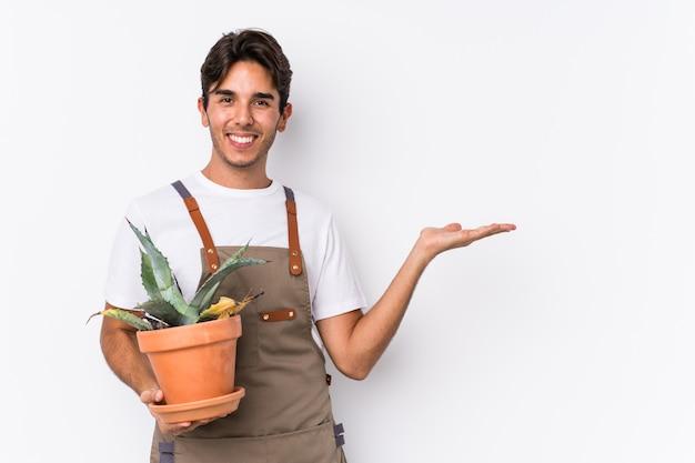Hombre caucásico joven jardinero sosteniendo una planta aislada mostrando un espacio de copia en una palma y sosteniendo otra mano en la cintura.