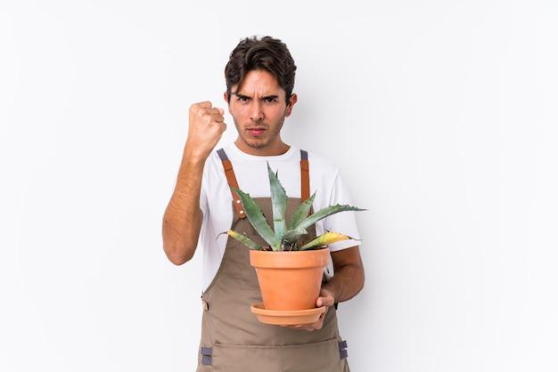 Hombre caucásico joven jardinero sosteniendo una planta aislada mostrando puño agresivo expresión facial.