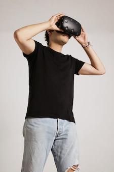 Hombre caucásico joven en jeans azul claro rasgados y camiseta negra sin etiqueta sostiene gafas vr en su rostro aislado en blanco