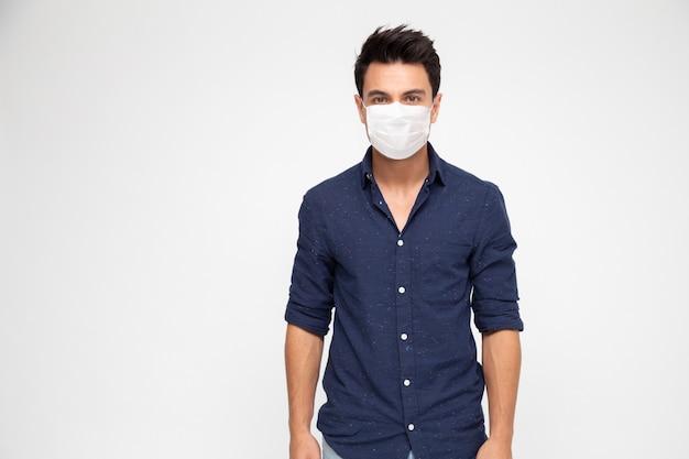 Hombre caucásico joven con mascarilla para proteger de covid-19 aislado en la pared blanca