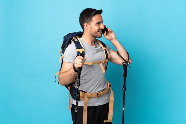 Hombre caucásico joven con mochila y bastones de trekking aislado en la pared azul manteniendo una conversación con el teléfono móvil
