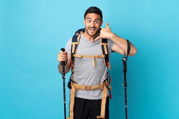 Hombre caucásico joven con mochila y bastones de trekking aislado sobre fondo azul haciendo gesto de teléfono. llámame señal
