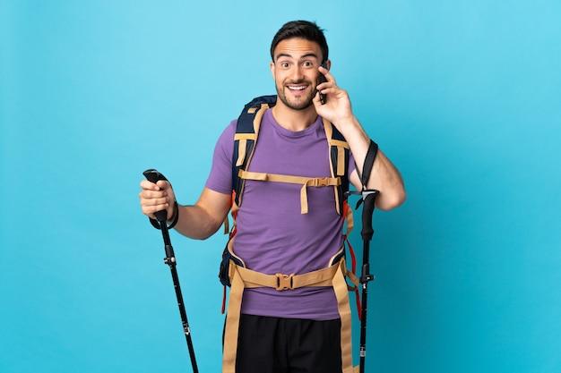 Hombre caucásico joven con mochila y bastones de trekking aislado sobre fondo azul manteniendo una conversación con el teléfono móvil con alguien