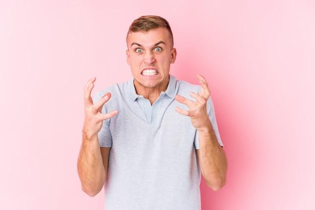 Hombre caucásico joven molesto gritando con las manos tensas.