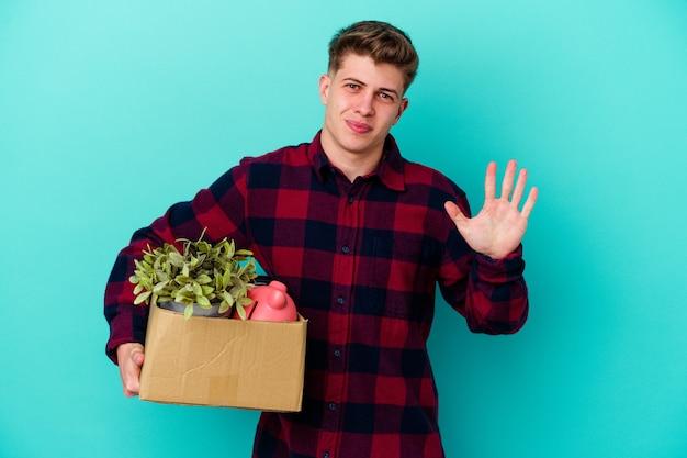 Hombre caucásico joven en movimiento sosteniendo una caja aislada sobre fondo azul sonriendo alegre mostrando el número cinco con los dedos.