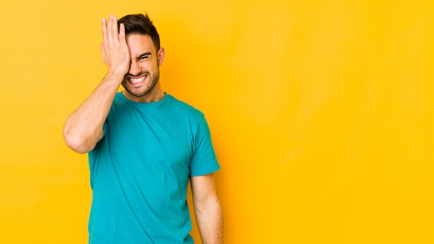 Hombre caucásico joven en la pared amarilla olvidando algo, golpeando la frente con la palma y cerrando los ojos.