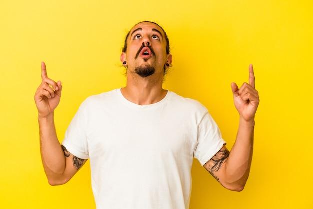 Hombre caucásico joven con el pelo largo aislado sobre fondo amarillo apuntando al revés con la boca abierta.